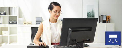 Image of a woman happily working at her computer.