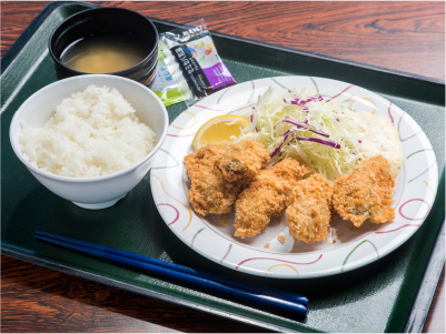 Photo: A menu selection with sustainable seafood. Deep-fried oysters from Miyagi Prefecture. White rice and miso soup served on a tray.