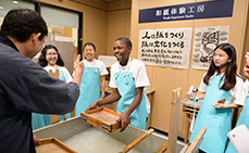 Photo: Instructor praising kids making Japanese paper well