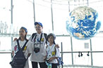 Photo: Thai girls taking a commemorative photo in front of the huge globe