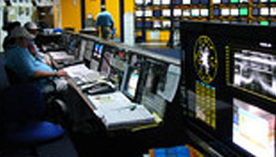 Photo: Staff working with multiple monitors in the main control room at the International Broadcast Center (IBC) for the Olympic Games Athens 2004