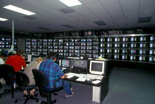Photo: Staff working with multiple monitors and broadcasting equipment at the International Broadcast Center (IBC)