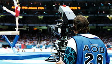 Photo: Cameraperson filming a gymnast's performance with a camera recorder at the gymnastics venue of the Olympic Games Atlanta 1996