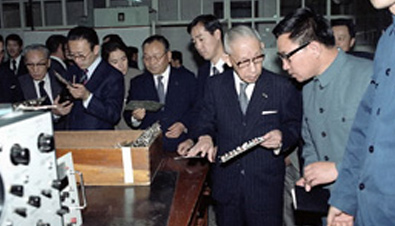 Photo: Panasonic founder Konosuke Matsushita talking to an attendant during a visit to China