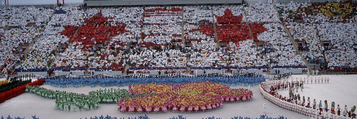 Photo: Spectators forming maple leaves in the main stand and performance by colorfully dressed dancers on the stadium's ground at the opening ceremony of the Olympic Winter Games Calgary 1988