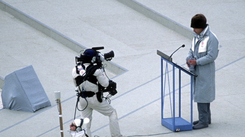 Photo: Cameraperson filming a person giving a speech at the opening ceremony of the Olympic Winter Games Calgary 1988
