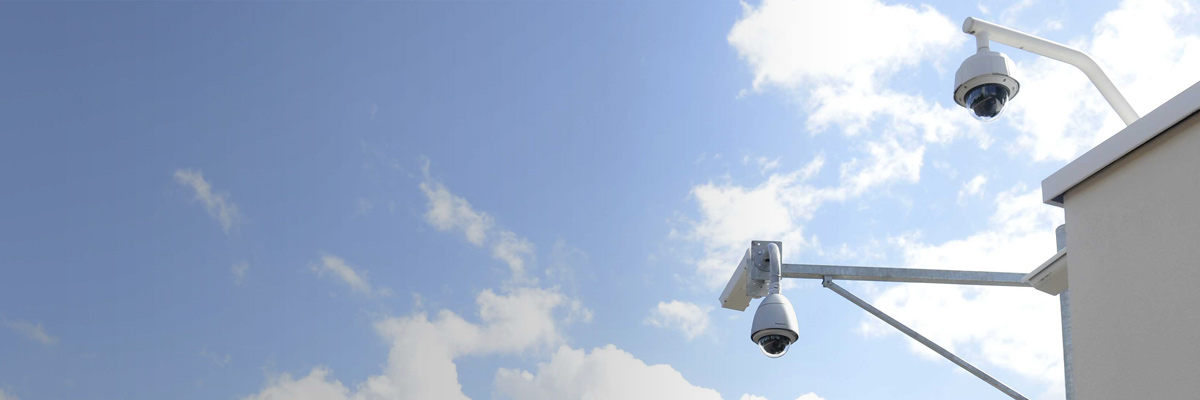Photo: Outdoor security camera with housing and dome-type security cameras installed on the outside of a building