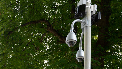 Photo: Outdoor security cameras with housing installed on a post outdoors
