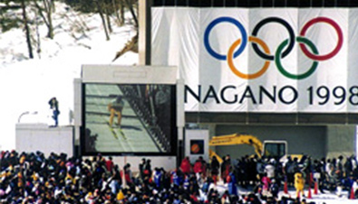 Photo: Ski jumping competition being shown on an ASTROVISION large display unit installed at one of the skiing venues of the Olympic Winter Games Nagano 1998