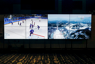 Photo of ice hockey competition footage and the ski competition venue shown on a split-screen system display