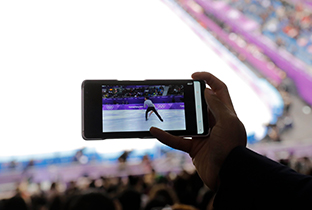 Photo of a spectator watching figure skating footage streamed to a smartphone in the stands at a competition venue