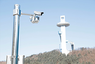 Photo of a security camera with integrated housing lens installed on an outdoor post