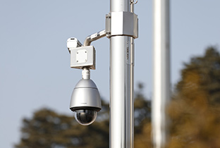 Photo of a security camera with integrated outdoor housing installed on an outdoor post