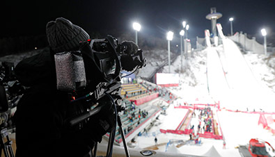 Photo of a broadcast cameraman using an HD camera recorder in freezing conditions at the PyeongChang 2018 Winter Games ski jump venue