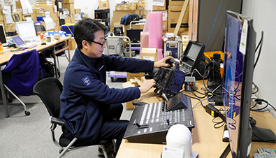 Photo of staff performing maintenance on camera recorders and other equipment at the Panasonic support room inside the International Broadcast Centre