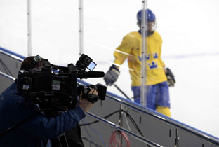 Photo: Cameraperson using an HD camera recorder at an ice hockey venue of the Olympic Winter Games Sochi 2014