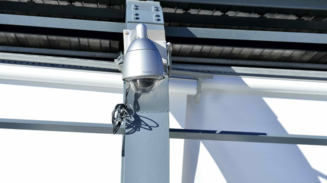 Photo: Outdoor security camera with housing installed on the outside of a building