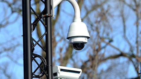 Photo: Dome-type security camera installed on a post outdoors