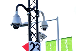 Photo: Outdoor security camera with housing and dome-type security camera installed on a post near a venue of the Olympic Winter Games Vancouver 2010