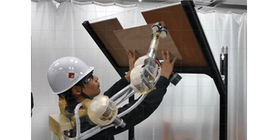 Photo: While a wearable robot arm holds a board, a worker cannail-up it